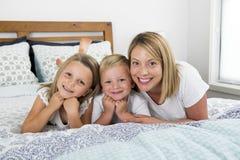 Jonge blonde Kaukasische vrouw die op bed samen met haar liggen weinig snoepjes 3 en 7 jaar het oude zoon en dochter speels gliml Stock Afbeelding