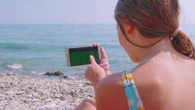 Jonge blonde Kaukasische vrouw het lopen smartphone tegen het overzees stock video