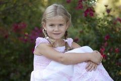 Jonge blonde meisjeszitting in een bloemtuin met s Royalty-vrije Stock Fotografie