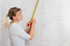Jonge blonde met maatregel in handen Stock Foto