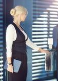 Jonge blonde onderneemster die de deur openen stock afbeeldingen