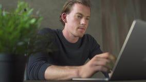 Jonge blonde ongerust gemaakte mensenzitting in de bureaulijst en het werken bij notitieboekje Het knappe zakenman typen op lapto stock footage