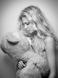 Jonge blonde sensuele vrouw die een reusachtige teddybeer bekijken Mooi meisje die een over gerangschikt stuk speelgoed houden Aa Stock Afbeelding