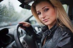 Jonge blonde vrouw in auto stock foto's