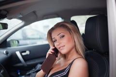 Jonge blonde vrouw in auto stock afbeelding
