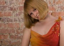 Jonge blonde vrouw dichtbij bakstenen muur Royalty-vrije Stock Afbeelding