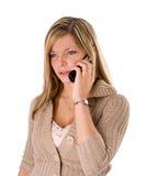 Jonge blonde vrouw die bij telefoon het fronsen spreekt royalty-vrije stock fotografie