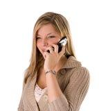 Jonge blonde vrouw die bij telefoon het glimlachen spreekt stock afbeeldingen