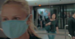 Jonge blonde vrouw die chirurgisch masker in de ingang van kliniek dragen Hongkong, China stock videobeelden