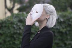 Jonge blonde vrouw die een masker opstijgen Bewerend om te zijn iemand anders concept outdoors royalty-vrije stock afbeelding