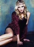 Jonge blonde vrouw die kroon in het binnenland van de feeluxe met em dragen Royalty-vrije Stock Fotografie