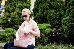 Jonge blonde vrouw die naar materiaal in haar handtas zoeken stock afbeelding