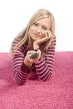 Jonge blonde vrouw die op het roze tapijt met afstandsbediening ligt royalty-vrije stock afbeeldingen