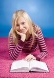 Jonge blonde vrouw die op het roze tapijt met boek ligt royalty-vrije stock afbeelding