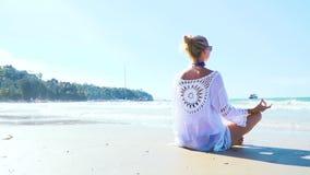 Jonge blonde vrouw die yoga op het strand doen stock footage