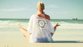 Jonge blonde vrouw die yoga op het strand doen stock video