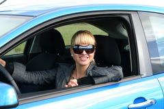 Jonge blonde vrouw in een auto stock foto's
