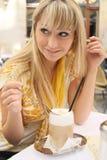Jonge blonde vrouw in een koffie met lattemacchiato Royalty-vrije Stock Afbeelding