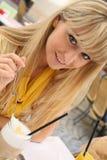 Jonge blonde vrouw in een koffie met lattemacchiato Stock Foto