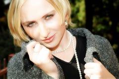 Jonge blonde vrouw in grijze woljasje en parels Royalty-vrije Stock Afbeeldingen