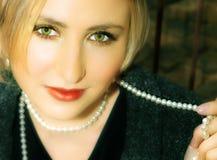 Jonge blonde vrouw in grijze woljasje en parels Royalty-vrije Stock Fotografie