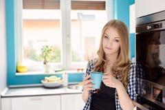 Jonge blonde vrouw het drinken thee of koffie stock afbeelding