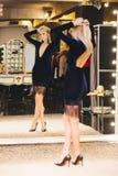 Jonge blonde vrouw in kleding het stellen bij grote spiegel Stock Foto