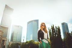Jonge blonde vrouw in leerjasje bij het wandelgalerijvenster stylish stock fotografie