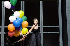 Jonge blonde vrouw met ballons stock afbeelding