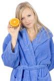 Jonge blonde vrouw met de helft van sinaasappel Stock Afbeelding