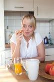 Jonge blonde vrouw met haar ontbijt Stock Afbeeldingen