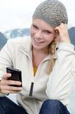 Jonge blonde vrouw met haar Smartphone in de hand Stock Afbeeldingen