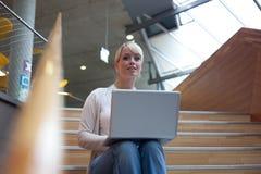 Jonge blonde vrouw met laptop Stock Foto's