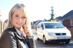 Jonge blonde vrouw met smartphone en taxi Stock Foto's