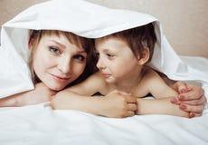 Jonge blonde vrouw met weinig jongen in bed, moeder en zoon, gelukkige familie Royalty-vrije Stock Afbeeldingen
