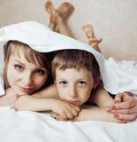 Jonge blonde vrouw met weinig jongen in bed, moeder en zoon, gelukkige familie stock foto's