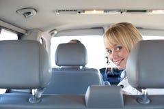 Jonge blonde vrouw op een achterbank van een auto Stock Foto