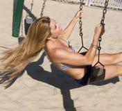 Jonge blonde vrouw op een schommeling bij het strand Stock Fotografie