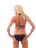 Jonge blonde vrouw in zwarte bikini van rug stock foto