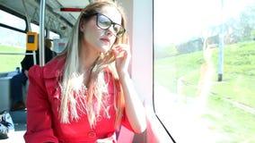 Jonge blonde vrouwen berijdende tram, die haar glazen schoonmaken stock video
