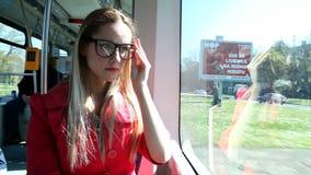 Jonge blonde vrouwen berijdende tram, die haar glazen schoonmaken stock footage