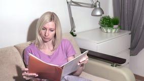 Jonge blonde vrouwenzitting op de bank en het doorbladeren de omslag stock video