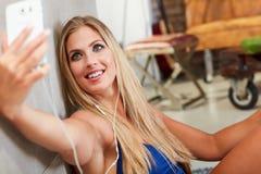 Jonge blonde witte vrouw die selfie thuis nemen stock fotografie
