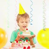 Jonge blondejongen in feestelijke hoed met stuk van verjaardagscake Stock Afbeelding