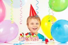 Jonge blondejongen in feestelijke hoed met verjaardagscake en ballons Stock Afbeeldingen