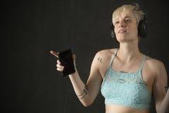 Jonge blondevrouw in blauwe camisole die met hoofdtelefoons dansen stock fotografie
