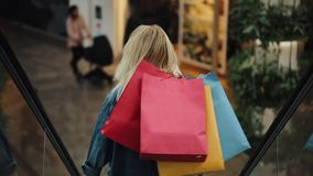 Jonge blondevrouw in de glimlachen die van het jeansjasje op de roltrappen in het winkelcomplex dalen stock video