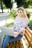 Jonge blondevrouw die aan laptop in het de zomerpark werken Royalty-vrije Stock Foto's