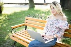 Jonge blondevrouw die aan laptop in het de zomerpark werken Stock Fotografie