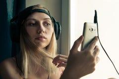 Jonge blondevrouw die aan muziek o luisteren stock afbeelding